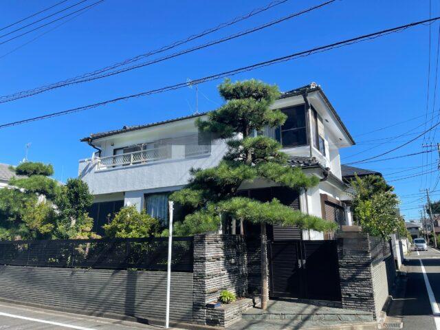 立派な植木のある、白い外壁の大きな家