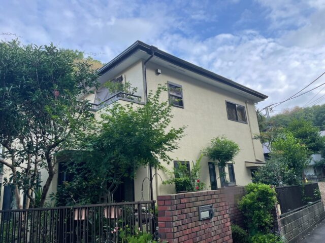 広い庭に聳え立つ、クリーム色の外壁の家