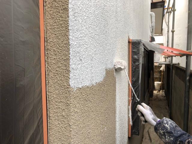 外壁に下塗りをする塗装職人