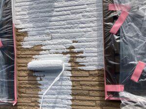 養生されている窓を避けながら、白色のペンキをローラーで塗装