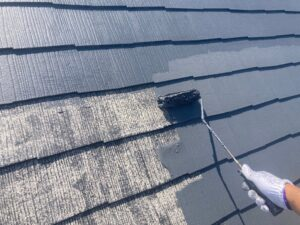 汚れた屋根に黒のペンキをローラーで塗装