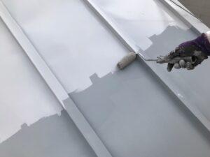 ローラーでグレーに塗装される屋根