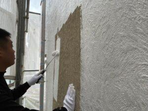 ローラーで茶色い外壁を白色に塗り替えている職人