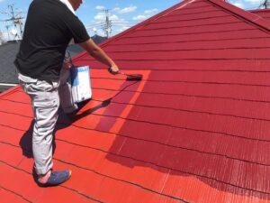 ローラーで赤の塗料を塗られている屋根