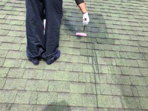 屋根の下塗りをしている職人