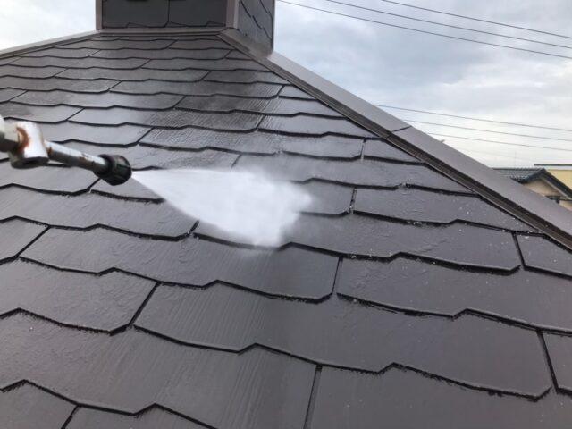 高圧洗浄機で洗浄される黒い屋根