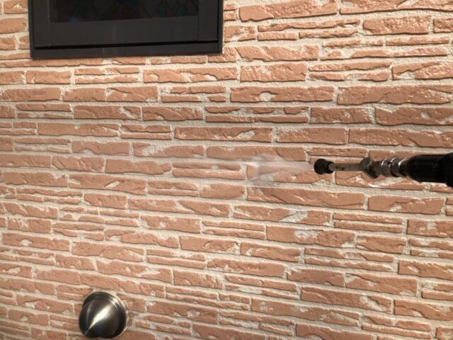 高圧洗浄機で洗浄されるベージュの外壁