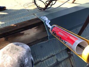 屋根補修にシリコンを塗っている