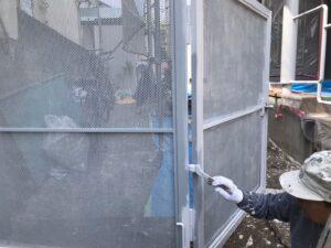 ハケで職人に塗装される門のドア