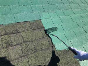 屋根をローラーで緑色のペンキを中塗り
