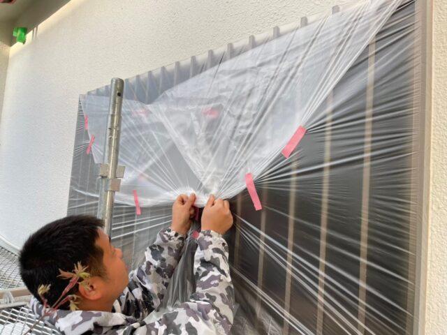 塗料が付着しないよう職人に養生される窓