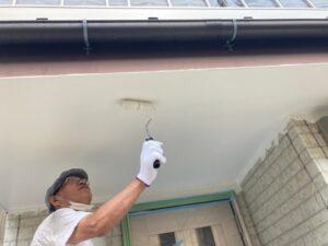 軒天をローラーで白く塗装する職人