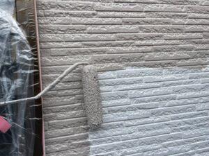 ローラーで灰色に塗装された外壁