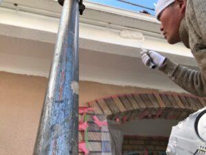 足場の上に乗った職人が軒天を白いペンキで塗装