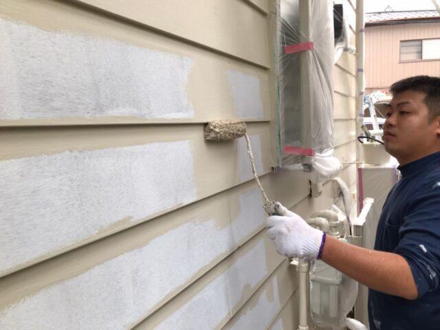 白色からクリーム色にローラーで塗装される外壁