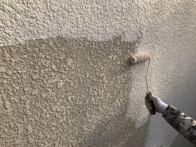 ローラーでクリーム色に塗られる外壁