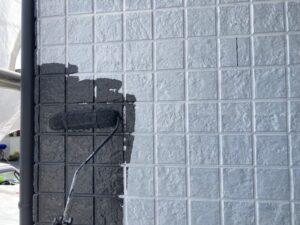 ローラーで黒く塗られる白いタイル面
