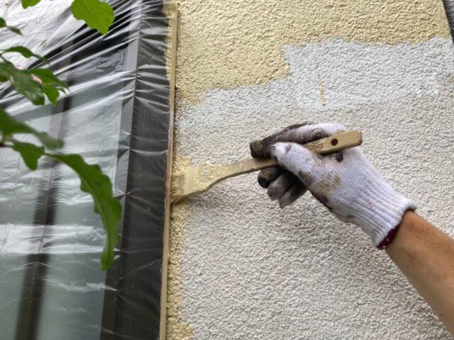 ハケで丁寧に塗装される窓の縁