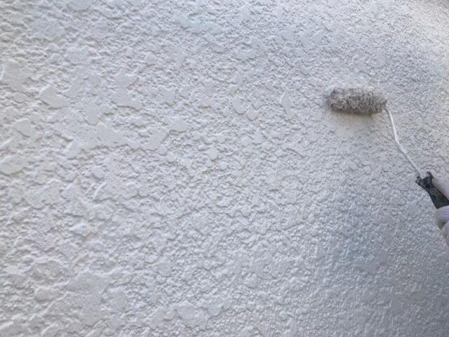 ローラーで白く塗られる外壁