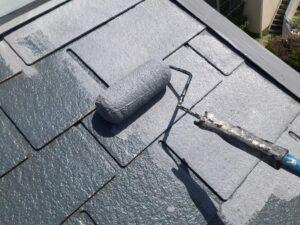 屋根にグレーの塗料をローラーで塗装