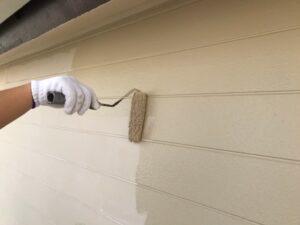 ローラーでクリーム色に塗られている外壁
