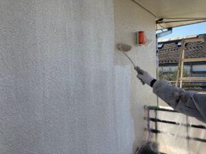 白い壁にベージュのペンキをローラーで塗装