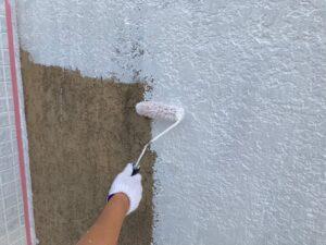 ローラーで白く塗られる茶色い外壁