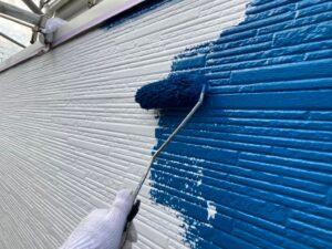白い外壁に青色のペンキをローラーで塗装