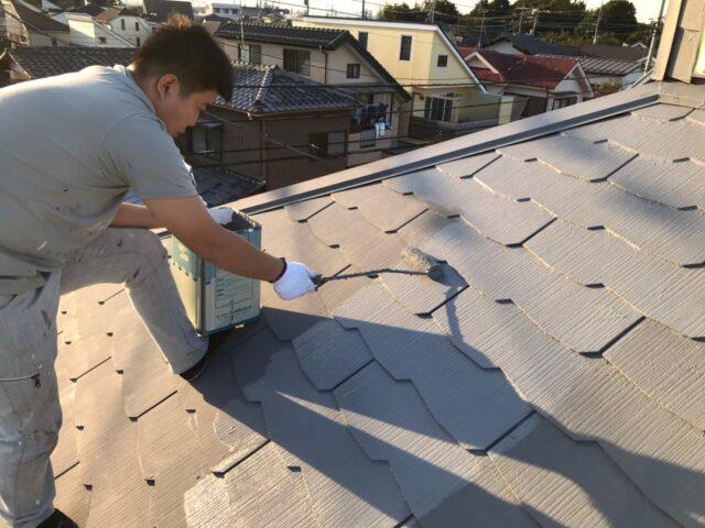 職人に中塗りされる黒い屋根