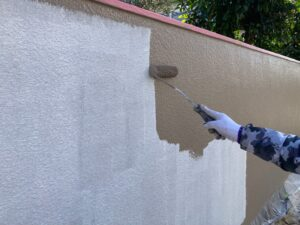 白い塀にベージュのペンキをローラーで塗装
