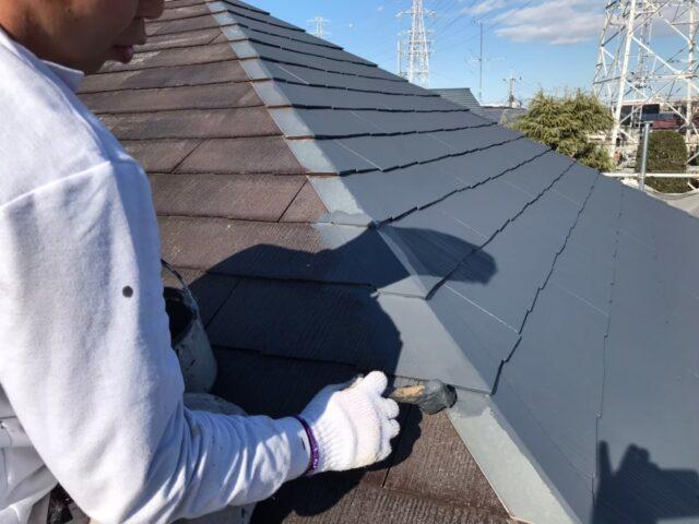 ハケでグレーに塗られる屋根の縁