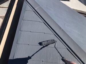 ローラーで黒く塗られる屋根
