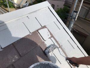 茶色い屋根にグレーの塗料をローラーで塗装