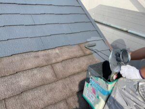 職人にローラーで塗装され、茶色からグレーになる屋根