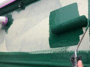 白い外壁に緑のペンキをローラーで塗装