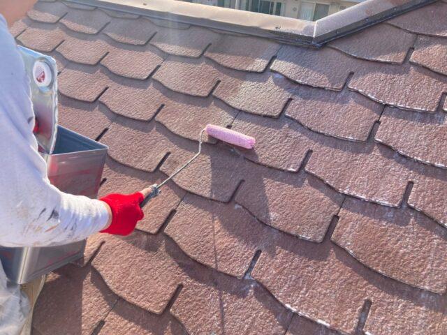 職人にローラーで下塗りされるピンクベージュの屋根