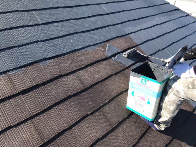 ローラーでグレーに塗装される茶色い屋根