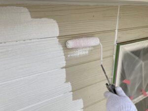 外壁をローラーで白色のペンキを塗装