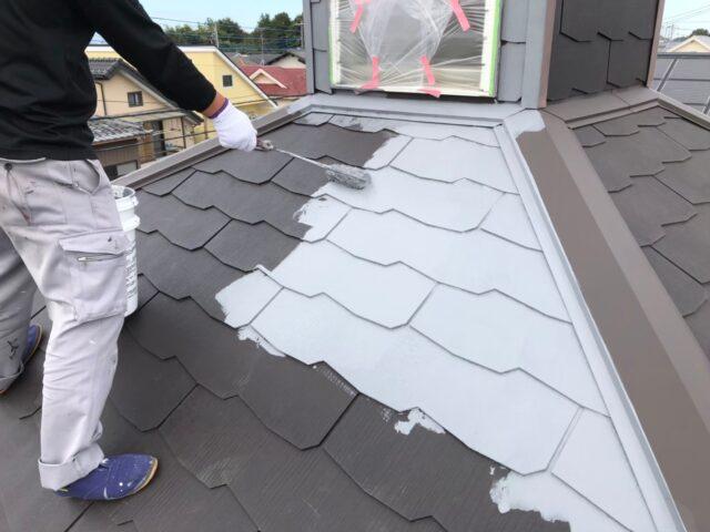 職人に白く塗装される屋根
