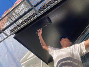 黒いペンキを軒天に塗装している職人