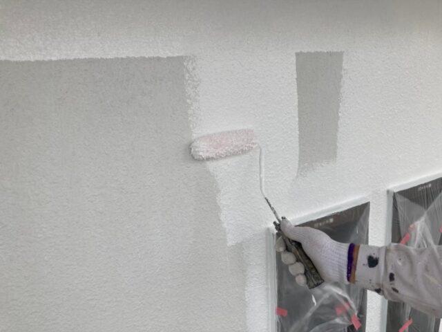 ローラーで白く塗装される外壁