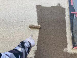 焦げ茶色の壁にベージュ色のペンキを塗装