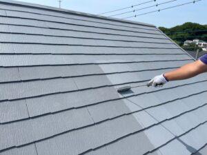ローラーで仕上げの塗装を施される屋根